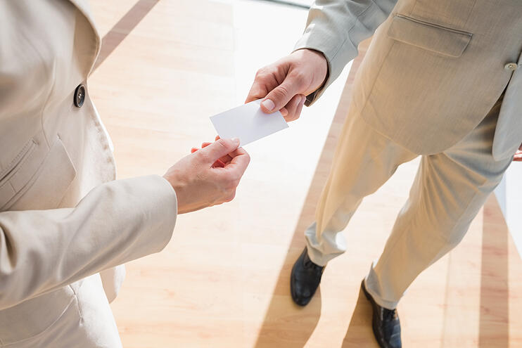 Businessman passing his card to businesswoman in an office