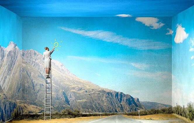Businesswoman standing on ladder drawing sun on wall