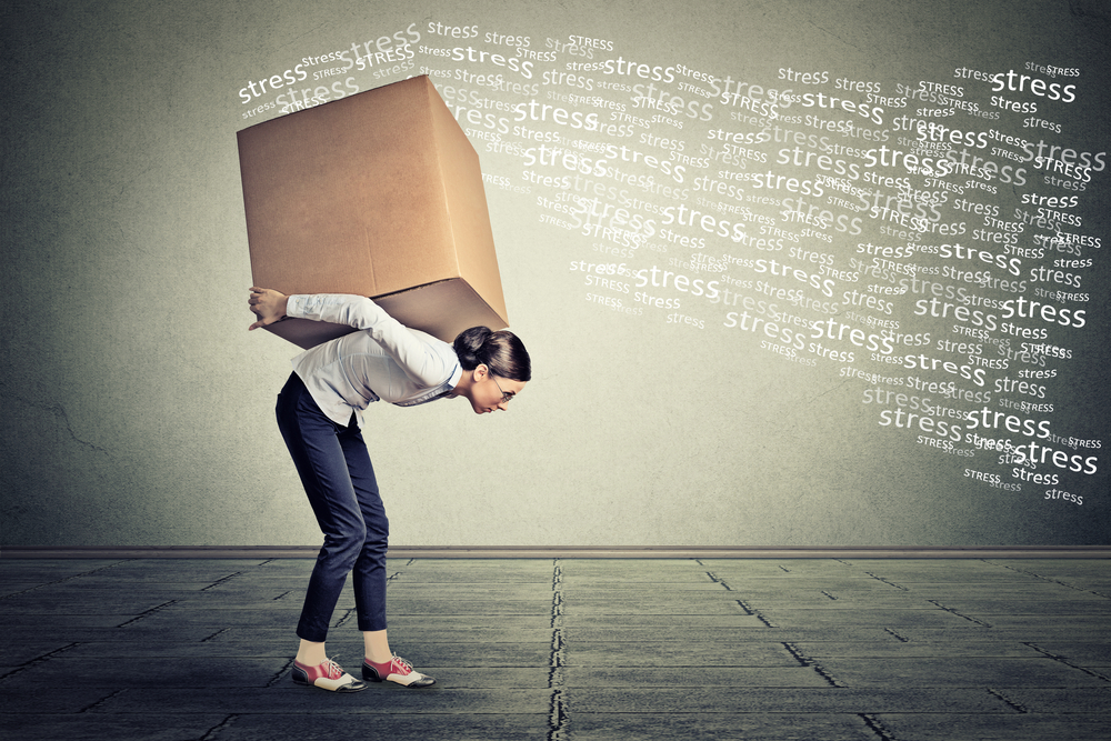 Stressed woman carrying on her back shoulders large box-1